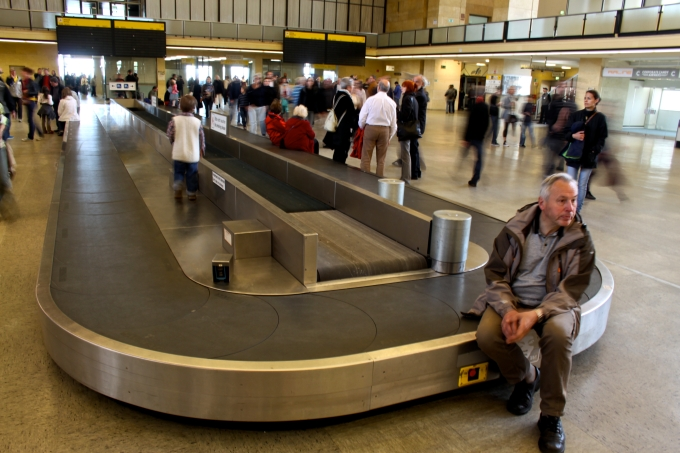 Le tapis à bagages immobile ne supporte plus de valises mais des touristes.
